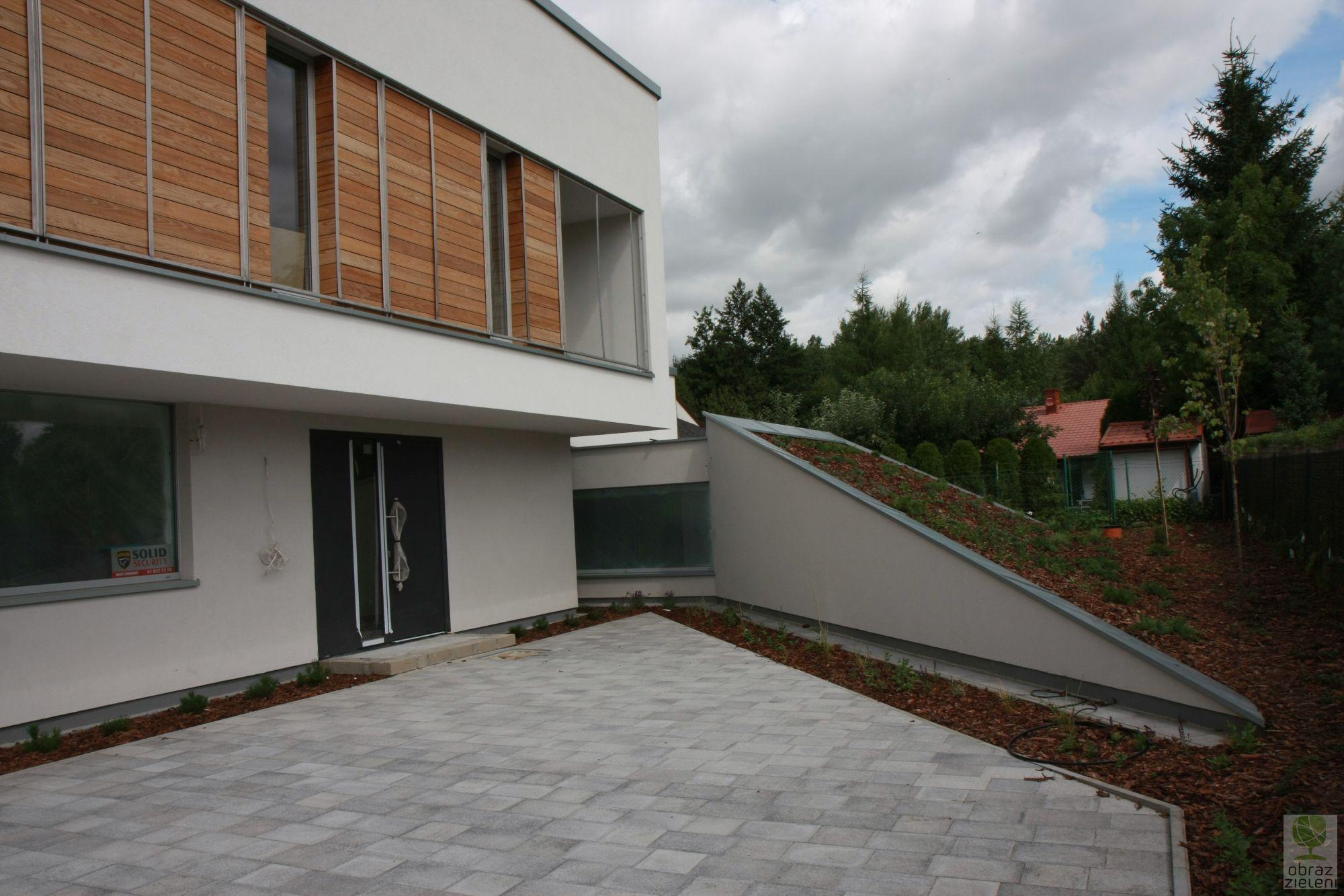 Ogród nowoczesny z odwróconym domem i zielenią na garażu