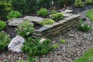 Ogród z murkami granitowymi i ścieżką z podkładów